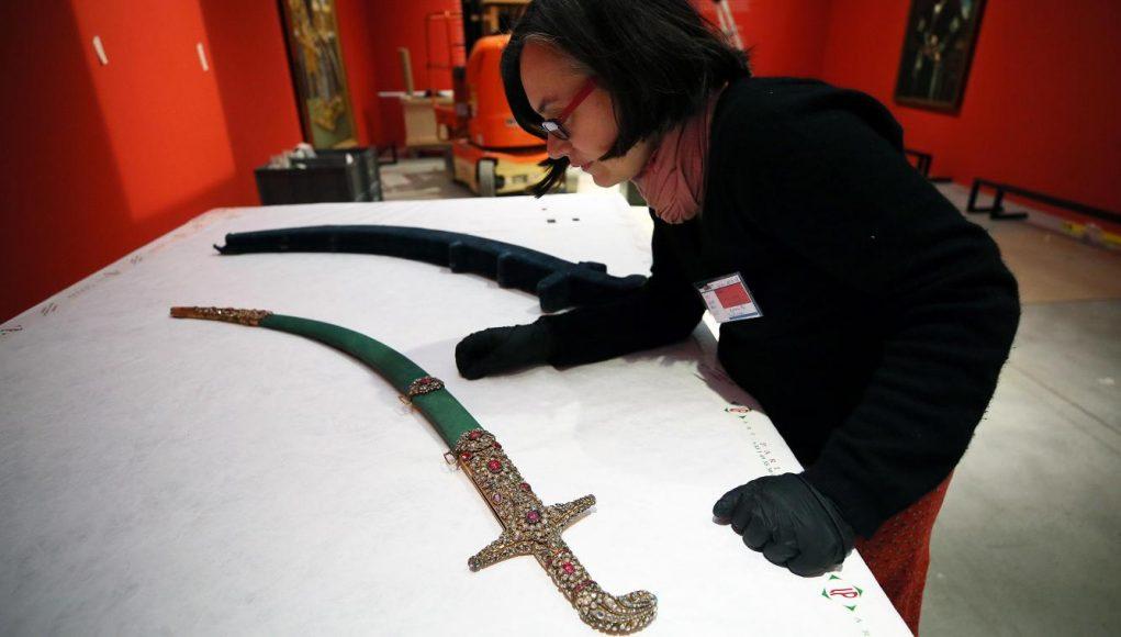 Gweanaelle Fellinger, commissaire de l'exposition L'Empire des roses, manipulant le sabre ayant servi au couronnement d'Ahmad Shah, monté sur le trône en 1909. Photo Séverine Courbe - VDNPQR